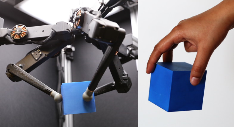 Picture of the robot holding a cube next to a human hand holding a cube
